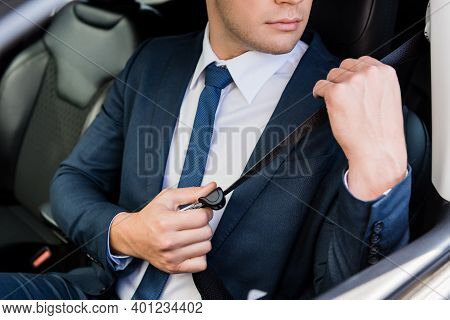 Cropped View Of Businessman Adjusting Seatbelt In Car On Blurred Background.