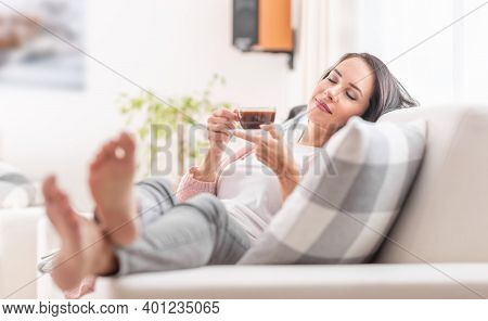 A Woman With Feet Up In Comfy Outfit Enjoys A Peaceful Time Of Relaxation On Her Sofa At Home.