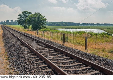 Rusty Railway Tracks Diagonally In The Picture. The Rails Are Mounted On Concrete Sleepers. There Ar