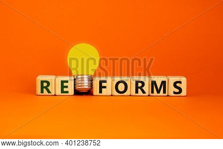 Reforms Symbol. Wooden Cubes With Word 'reforms'. Yellow Light Bulb. Beautiful Orange Background. Bu