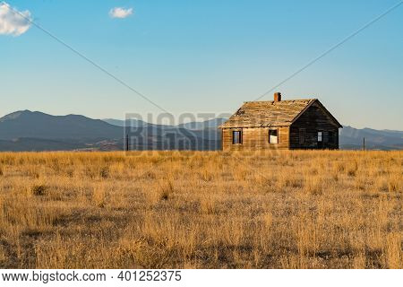 Abandoned Old Farm House Near The Rocky Mountains Of Colorado At Sunset