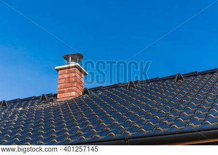 New Chimney Pipe In Red Bricks On Roof In Black Shingles. On Blue Sky. Construction Of A Family Hous