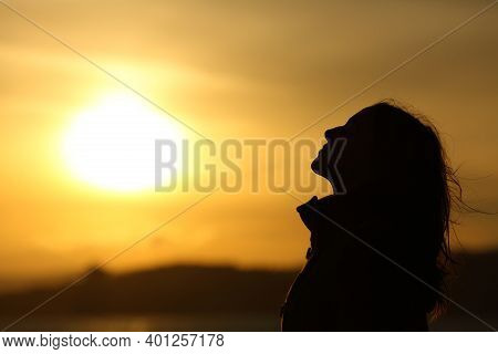 Side View Backlight Of Woman Silhouette Breathing Fresh Air At Sunset On The Beach