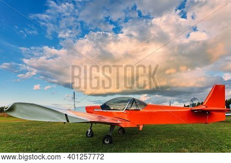 A small sports aircraft parked at the airfield at picturesque sunset