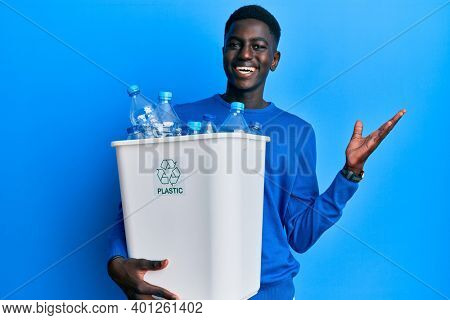 Young african american man holding recycling wastebasket with plastic bottles celebrating victory with happy smile and winner expression with raised hands