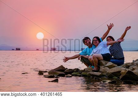 Asian Family Father Mother And Teenage Daughter Happy Sitting On The Waterfront At Lake Water Sun In