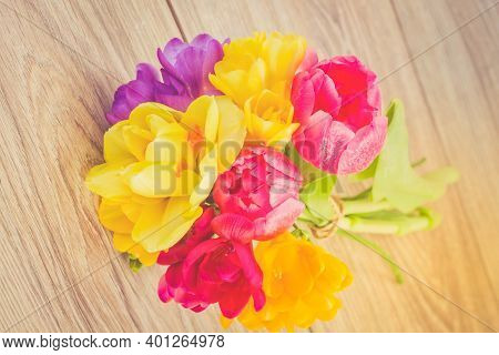 Posy Of Pink Tulips, Yellow Daffodils And Freesea Flowers On Wooden Table, Toned