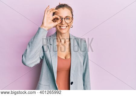 Beautiful caucasian woman wearing business jacket and glasses doing ok gesture with hand smiling, eye looking through fingers with happy face.