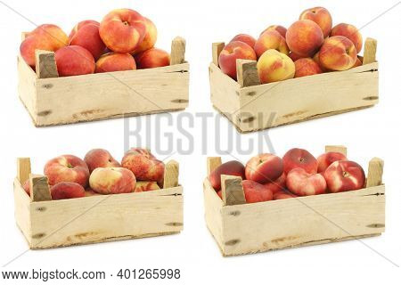 Fresh peaches and flat peaches (donut peaches) in a wooden crate on a white background