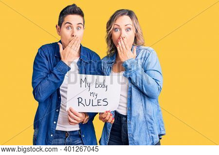 Couple of women holding my body my rules banner covering mouth with hand, shocked and afraid for mistake. surprised expression