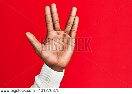 Arm and hand of african american black young man over red isolated background greeting doing vulcan salute, showing hand palm and fingers, freak culture