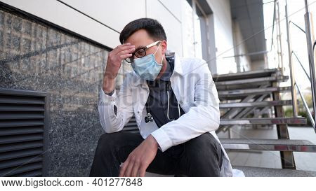 Caucasian Young Doctor Man Sits Down On The Stairs Near The Clinic Building, Tired And Unhappy Rubbi