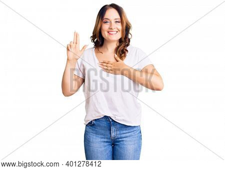 Young beautiful caucasian woman wearing casual white tshirt smiling swearing with hand on chest and fingers up, making a loyalty promise oath