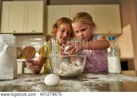 Two Cute Little Children, Boy And Girl In Aprons Looking Focused While Adding Eggs, Preparing Dough