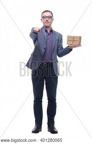 Cheerful handsome well-dressed young man in glasses holding gift box and looking at camera with smile