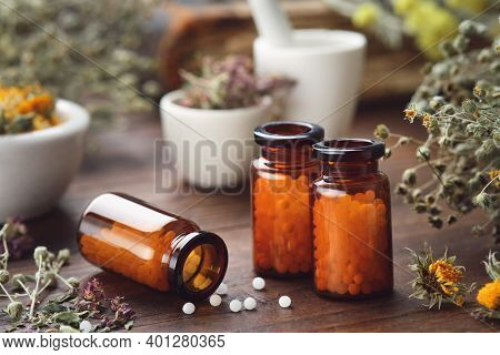 Three Bottles Of Homeopathic Globules And Medicinal Herbs. Homeopathy Medicine Concept.