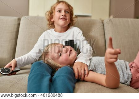 Portrait Of Cute Little Siblings, Boy And Girl Looking Focused While Watching Tv Together, Cuddling