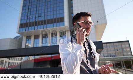 Portrait Of Tired Exhausted Doctor Having Phone Call Outside Hospital In Morning. Covid-19, Coronavi