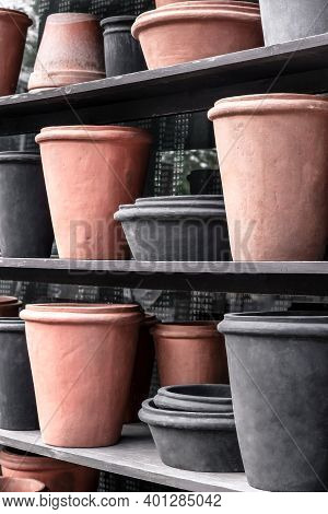 Pink And Black Clay Flowerpots On A Shelf, In A Flower Shop.