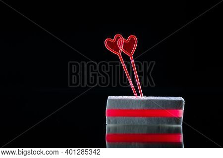 White Sugar Candy With Layer Of Red Marmalade And Two Heart Shaped Skewers On A Black Background Wit