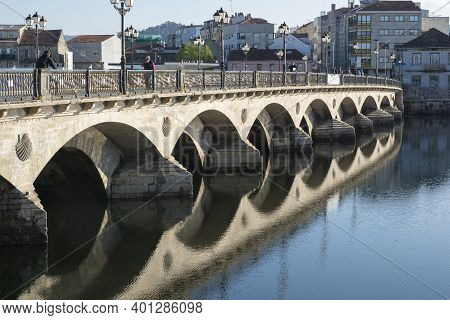 Spain, Pontevedra - May 11, 2019: Famous Ancient Bridge Across River With Reflection In Still Water.