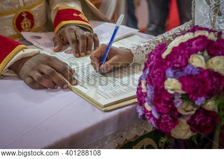 Kerala, India, 08-12-2017. Bride Signing The Book To Give Formal Consent To The Ceremony. Catholic W
