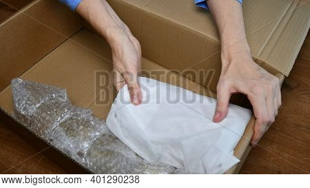 Woman Hands Pack Up Fragile Tableware Into Cardboard Box And Fix Wrapped Household Items Inside. Pre
