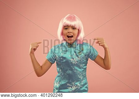 Look At This. Unhappy Girl Pointing Fingers At Wig. Small Child Pointing Pink Background. Fashion An