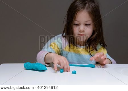 Little Girl Playing With Colorful Clay. Cute Child Girl Sits At The Table And Plays With Plastiline
