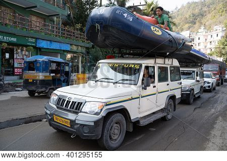 Rishikesh, India - Feburay 22, 2020: Car Carrying A Whitewater Rafting Boat Drives Through The Stree