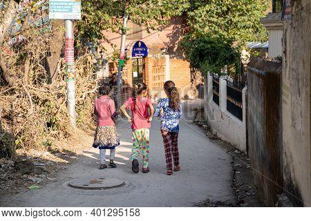Rishikesh, India - Feburary 22, 2020: Three Teenage Indian Girls Walk Down An Alley In The City, Bac