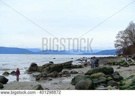 Wreck Beach, Vancouver, Canada - December 20th, 2020: People Walking Along The Beautiful Sandy Beach