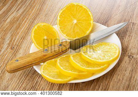 Whole Lemon, Half Of Lemon, Kitchen Knife, Few Slices Of Lemon In Glass White Saucer On Brown Wooden
