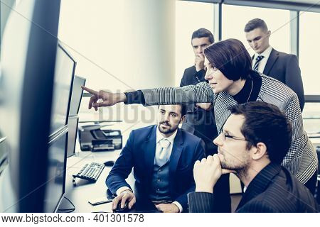 Business Team Looking At Data On Multiple Computer Screens In Corporate Office. Businesswoman Pointi