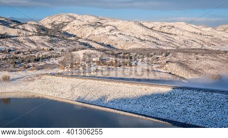 mountain lake and dam at foothills of Rocky Mountains in sunrise light, Horsetooth Reservoir - a popular recreational area in northern Colorado