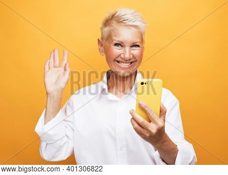 It's selfie time. Image of cheerful mature old woman standing isolated over yellow background wall talking by mobile phone.