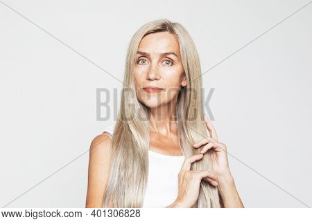 Beauty, fashion and old people concept: beautiful elderly woman with long lovely gray hair stroking her hair, shampoo and healthy hair concept over light grey background
