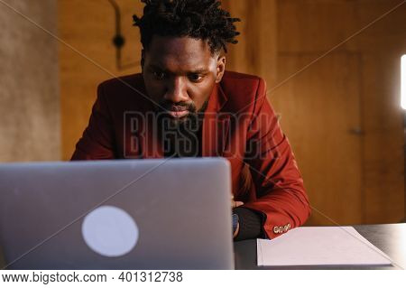 A Focused Black Man In A Suit Is Working On A Laptop. Remote Work From Home