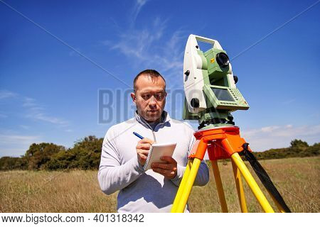 Man Surveyor At Work And Using Of Total Station. Survey Instrument Geodetic Device, Total Station Se