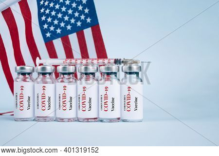 Covid-19 Vaccine Vials Against Usa Flag On Blue Background With Copy Space For Text - Coronavirus Va