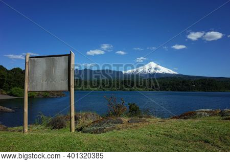 Blank wooden information board with view of snow capped Villarrica volcano and lake Villarrica. Nature of Chile. Pucon