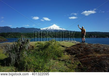 Man tourist standing with hand up posing for photo with view of snow capped Villarrica volcano and lake Villarrica. Nature of Chile. Tourism in Pucon
