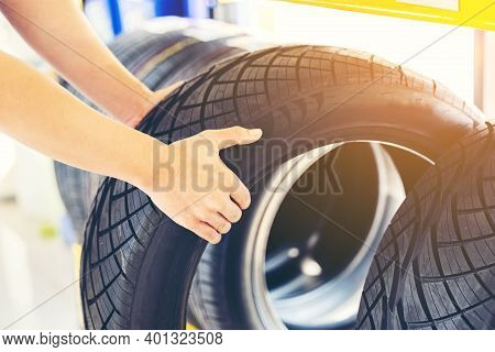 Retirement Man Touching And Choosing For Buying A Tire In A Supermarket Mall. Measuring Rubber Car W