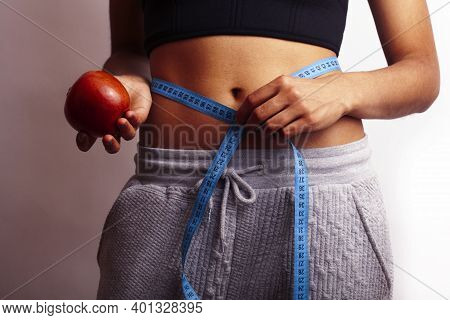 Woman Measuring Waist With Tape On Knot, African Tan Isolated On White Background, Holding Red Apple