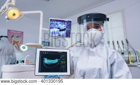 Doctor Showing Digital X-ray On Tablet In Dental Office With New Normal, Explaining Teeth Treatment.