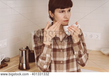Covid-19 Causes Loss Of Smell. Woman Sniffing Smell Of Coffee From Cup While Preparing Drink In Morn