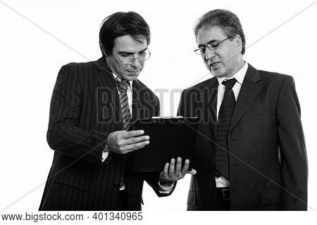Young Persian Businessman Reading On Clipboard Together With Senior Persian Businessman