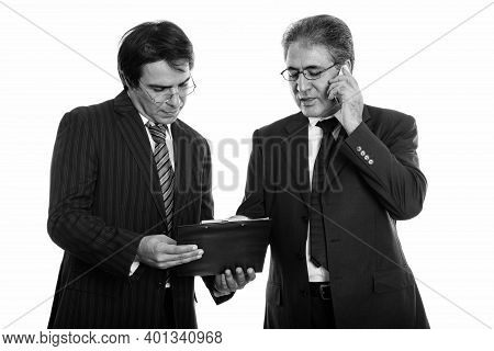 Young Persian Businessman Reading On Clipboard Together With Senior Persian Businessman Talking On M