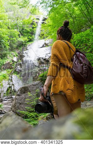 Wellbeing Photographer Enjoying Splash Of Hidden Waterfall. Fit Lady Hold Camera On Hand Traveling A