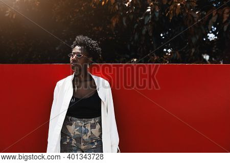A Gorgeous Stylish Young Black Woman With Curly Afro Hair, In An Elegant White Trench And Camouflage